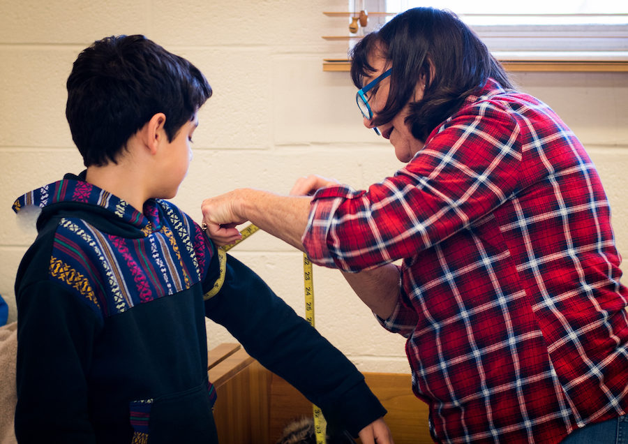 Young actor is measured for costume by adult volunteer.
