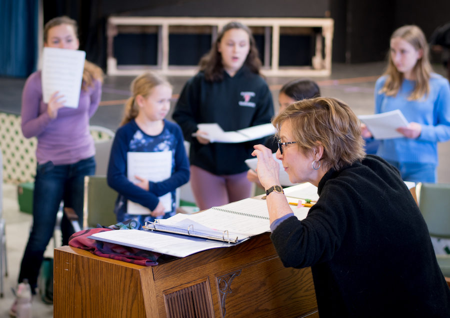 Youth actors rehearse music with pianist/instructor.