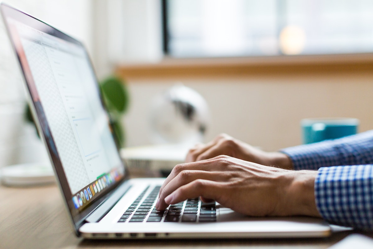 Photo of a laptop computer and the hands and wrists of a person using it.