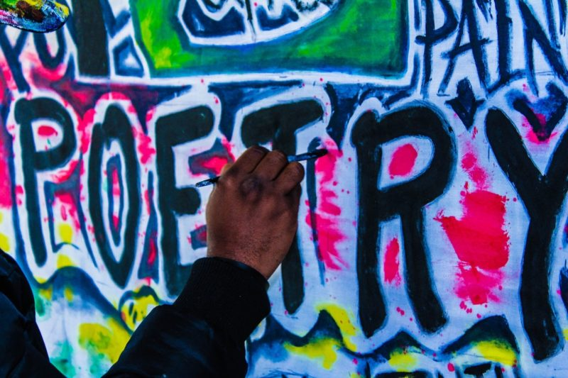 """A hand is shown painting the word """"poetry"""" graffiti-style on a wall."""