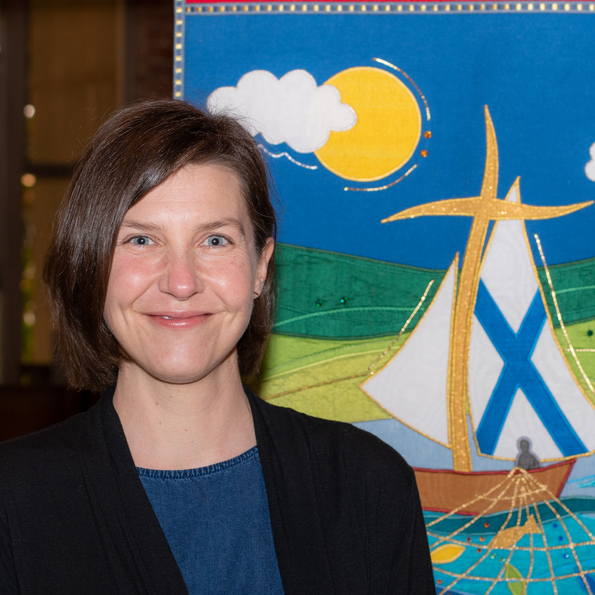 Emily Blecksmith is shown from the shoulders up, standing with the St. Andrew's banner.