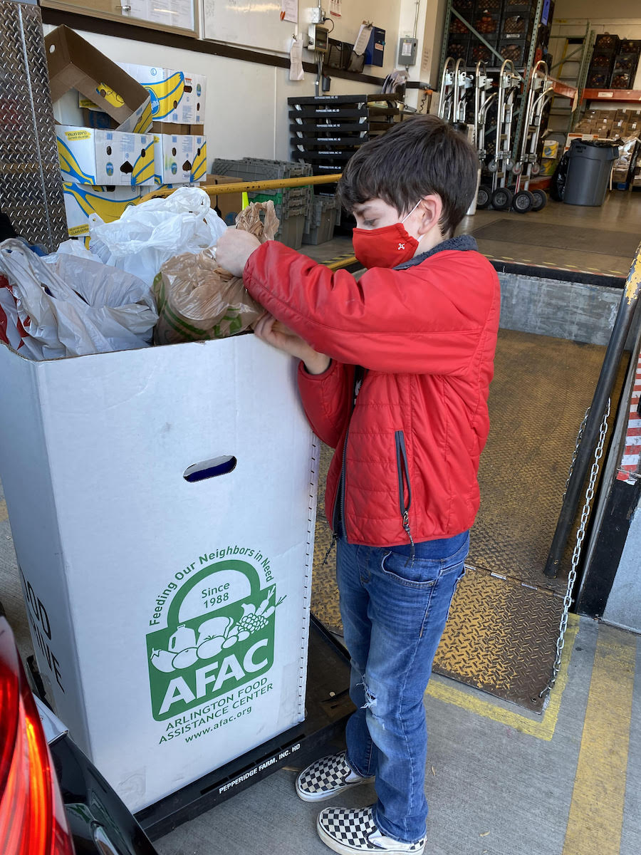 A boy in a red jacket and red mask places bags of donated food into a dropoff box at Arlington Food Assistance Center.