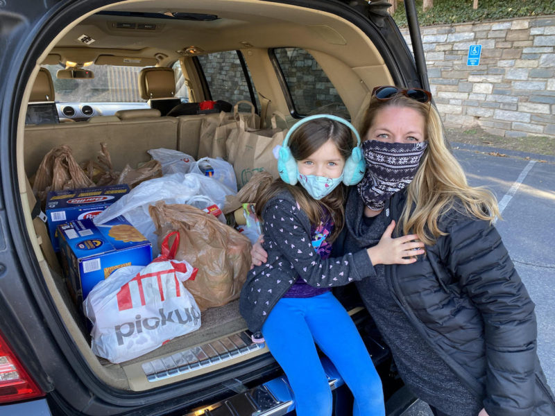 A masked woman and girl pose on tailgate of a car alongside boxes and bags of donated food in St. Andrew's church parking lot.