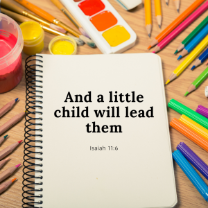 "A spiral-bound book is shown on a flat wooden surface with the Biblical quote ""And a little child will lead them."" It is surrounded by colored pencils , watercolors and paint brushes."