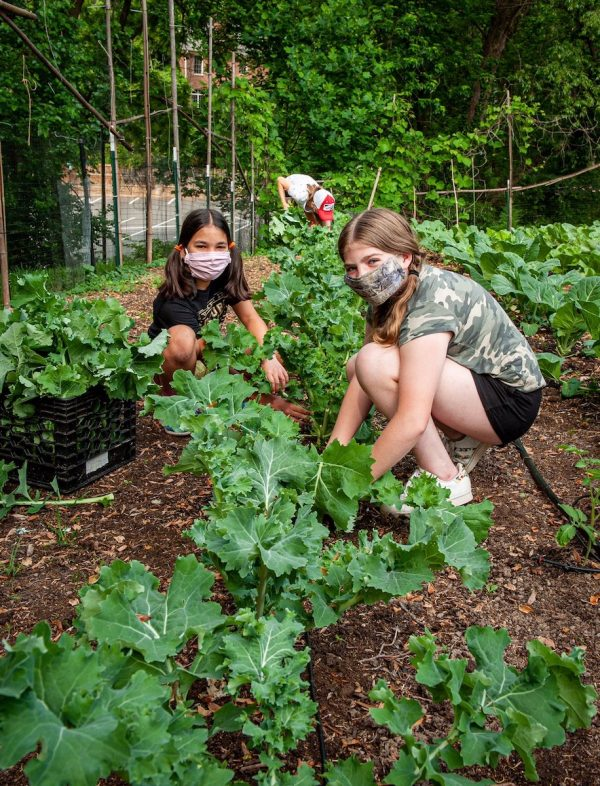 Two masked girls working in Garden of Hope.