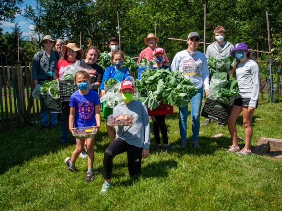Volunteers stand with harvested produce near Garden of Hope.